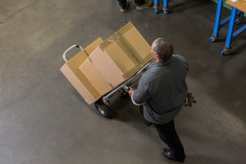 Worker carting boxes on hand truck in warehouse