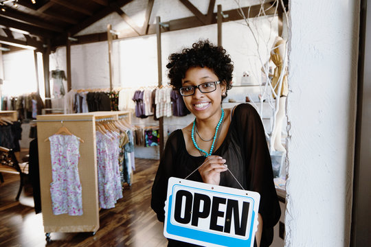 Mixed race woman putting open sign on door
