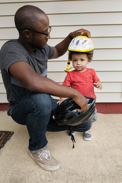 Father putting helmet on toddler son