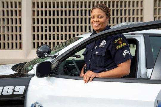 Policewoman standing in door of Police car looking towards camera smiling