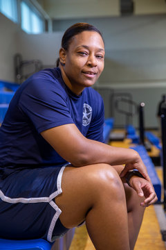 Portrait of Police woman sitting on bleachers in gymnasium looking towards camera smiling