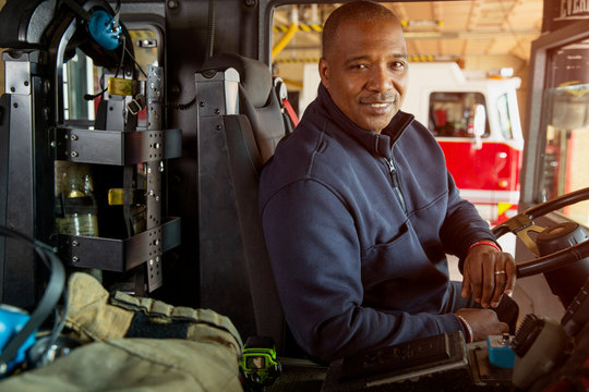 Portrait of fireman sitting in driver's seat of fire engine