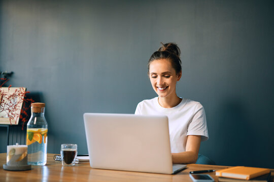 Smiling businesswoman using laptop on desk against wall in home office
