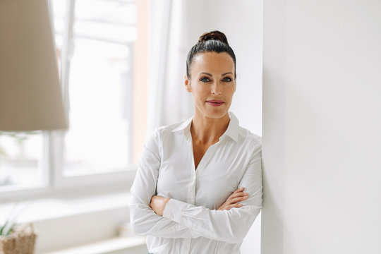 Confident female entrepreneur with arms crossed standing by wall in home office