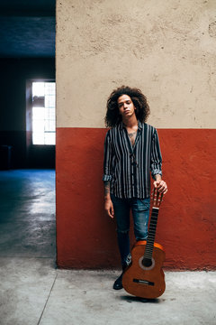 Mid adult man with curly hair holding guitar while standing against wall in city