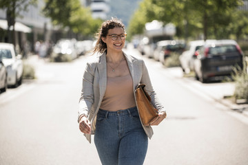 Smiling young woman with bag walking on road during sunny day