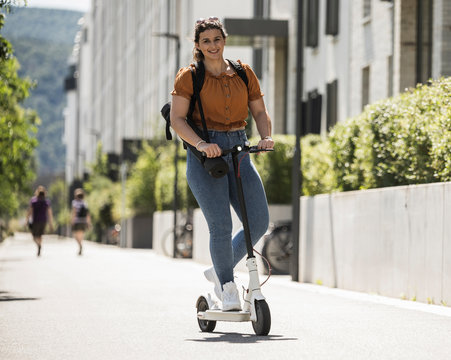 Smiling young woman riding electric push scooter on road during sunny day