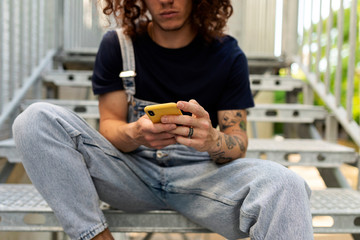 Man using mobile phone while sitting on steps