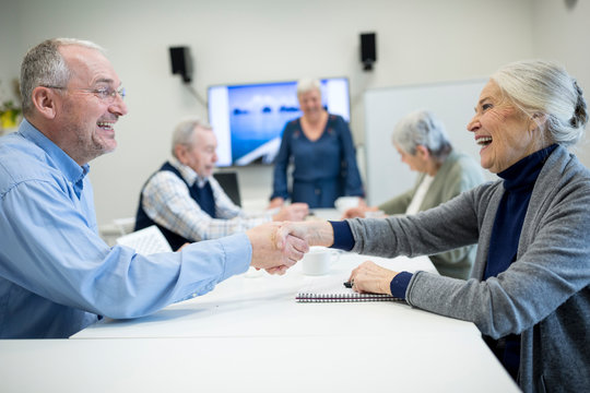 Senior citizens meeting at skill enhencement course, shaking hands