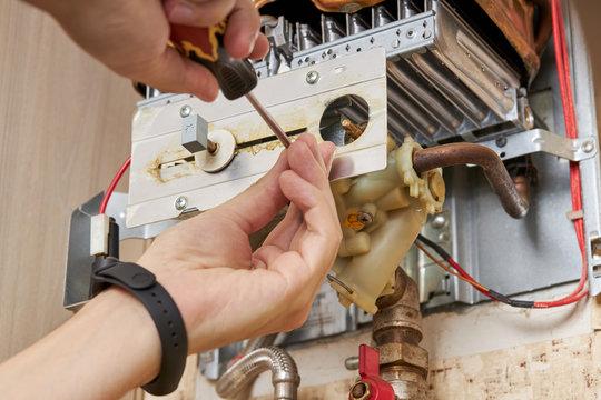 service technician repairing gas water heater indoors. water heater maintenance. diy concept