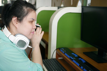 Asian young blind person woman with headphone using smart phone with voice assistive technology for disabilities persons in workplace with computer and braille display on table.