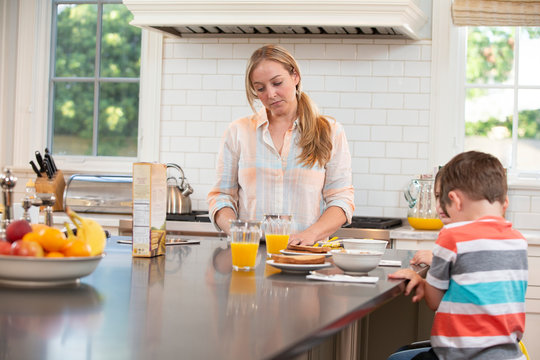 Mom who is feeling under the weather with kids in kitchen, struggling to get the kids breakfast and ready to start the day