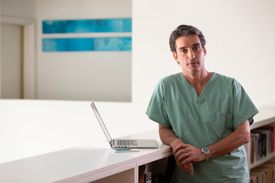 Portrait of Hispanic Male doctor in his home taking a break from practicing Tele-medicine