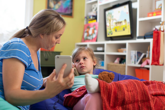 Mom with daughter who is not feeling well using cell phone to consult doctor and get advice via Telemedicine service