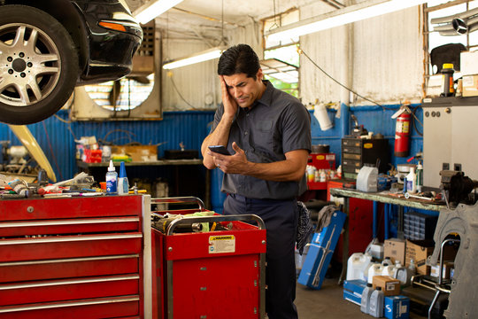 Hispanic car mechanic working in auto shop, feeling ill, using mobile phone to check in with tele-medicine doctor