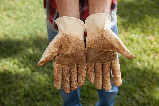 A man with dirty gloves holds his hands out