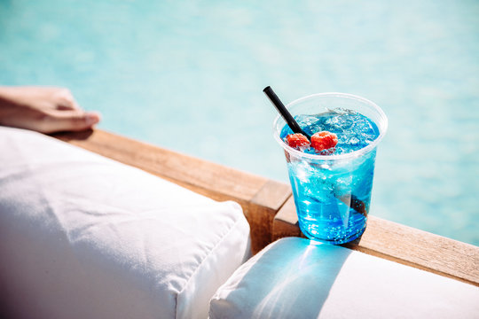 A blue cocktail poolside at a resort