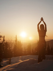 Woman standing on snow during winter sunrise, doing morning meditation in lotus pose