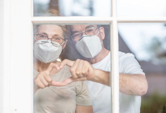 Elderly couple wearing protective face masks watch through their home window and show heart sign during the coronavirus epidemic