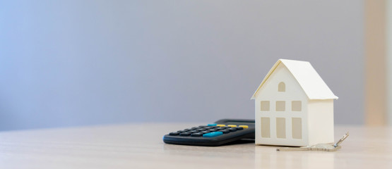close up house's model with calculator and key on table for expense of home loan mortgage and home utility , economy and financial concept