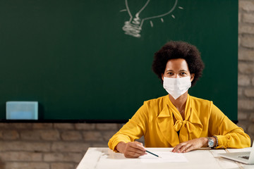 Black female teacher wearing face mask while giving a lecture in the classroom.