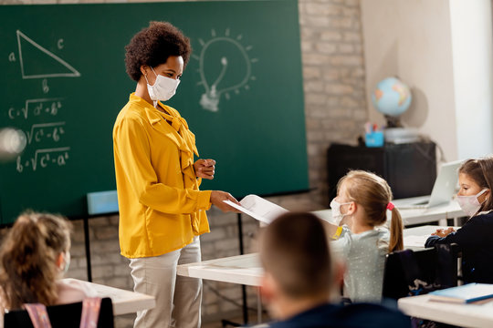 Happy black teacher giving exam paper to her student while wearing protective face mask in the classroom.