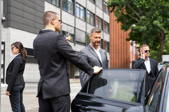 Bodyguards Protecting Businessman Opening Car Door