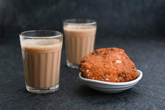 Top view of Indian Masala Chai and Parippu vada traditional milk tea beverage Kerala India. Two cups of organic ayurvedic or herbal drink India, good in winter for immunity boosting.