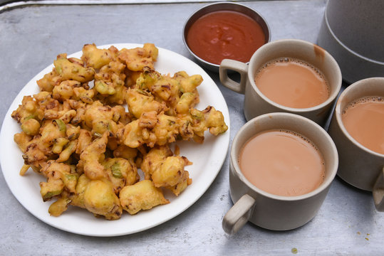 Indian milk tea, Chai, onion pakoda fried snack , North Indian Snacks popular deep fried hot spicy tea time food. Traditional food Ramadan, Eid, Iftar pary, Onam, Vishu. Local street food of India.