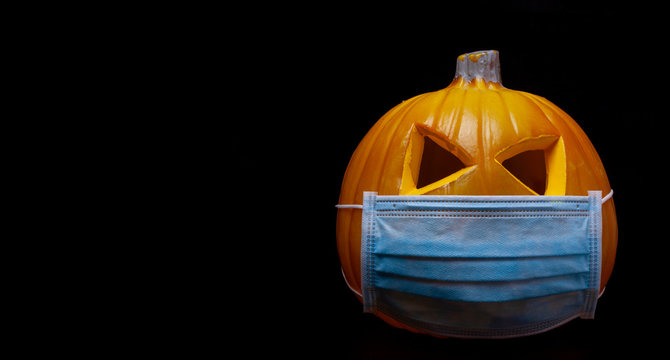 halloween in the age of coronavirus - pumpkin with face mask on black background