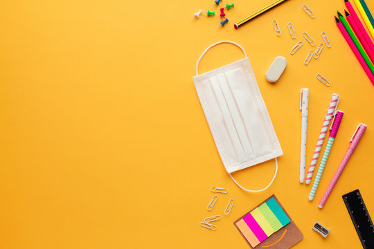 Stock photo of back to school concept in the new normal with a face mask, some stationery objects and copy space on the left