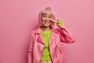 Lovely smiling young Asian woman with pink hair makes v sign for peace, shows two fingers over eye, dressed in fashionable clothes, isolated over rosy background. People, body language concept