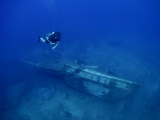 scuba divers exploring shipwreck scenery underwater ship wreck deep blue water ocean scenery of metal underwater and fish around