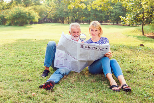Happy couple elder reading the business newspaper together through a magnifying glass. Elderly picnic in the garden at the sunshine day. Retirement, Picnic, Older,  Age-Related Macular Degeneration.