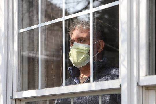Man wearing mask inside staring out the window