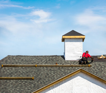 Roofer attaching shingles on a rooftop of a new building