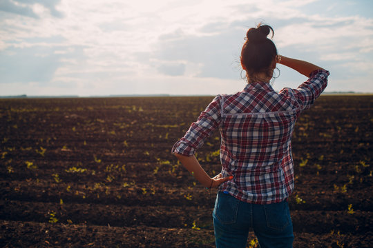 Woman farmer standing and looking agricultural field soil.