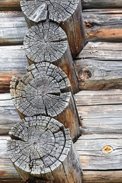 old log ends of a wooden rural house with cracks