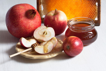 Rosh Hashanah holiday, greeting card, background with a jar of honey, pomegranate, apples, a plate with slices and honeycomb on a white wooden table.