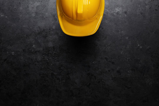Bright yellow hard hat on dark black background. Contractor or Under Construction background.