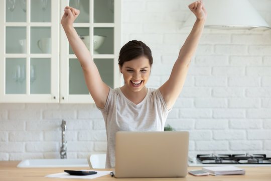 I did it. Happy millennial woman employee working online by laptop from home is excited of achieving good sales, young female student is surprised getting email from college with perfect exam results