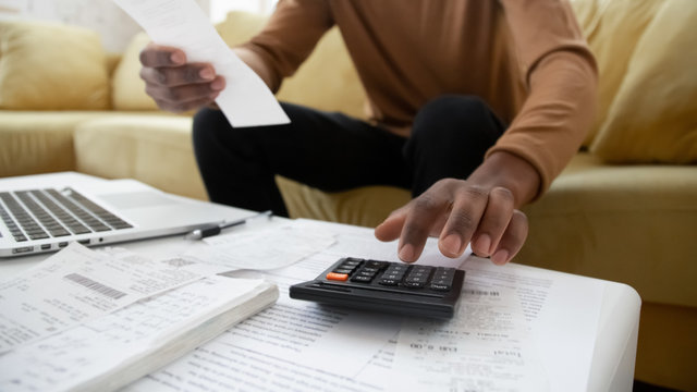 Black small business owner making calculations at home. Close up of african american man checking bills, counting expences, examining credit balance or planning household sitting on sofa in living