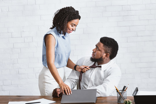 Sexual molesting at work. Black woman pulling her subordinate by his tie in company office