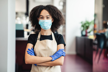 African american girl hairdresser in protective mask posing at salon