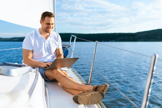 Happy Man On Yacht Sitting With Laptop Working On Sailboat