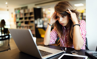 Young depressed tired woman working studying on notebook