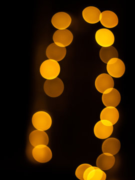 Golden bokhe at night with back black background.