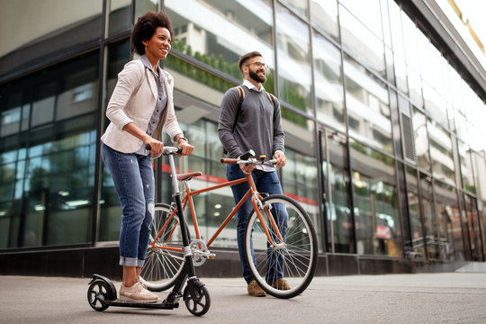 Two smiling business people driving electric scooter, bicycle going to work.
