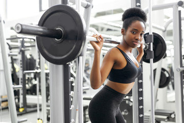athletic african woman pumping up muscles with barbell, crossfit weightlifting or deadlifting workout training in the gym
