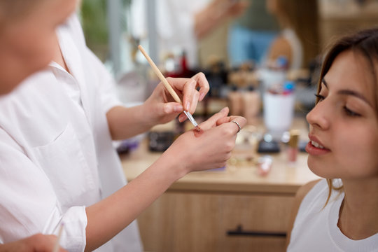 professional make-up artist or visagist apply cosmetics on hand before applying it on face, in beauty salon